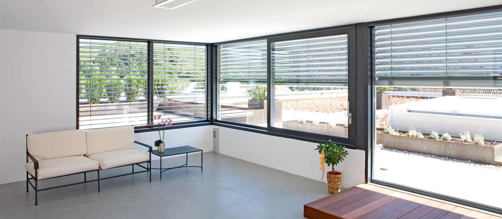 Wohnraum mit Blick nach draußen durch leicht abgedunkeltes Alu-Fenster