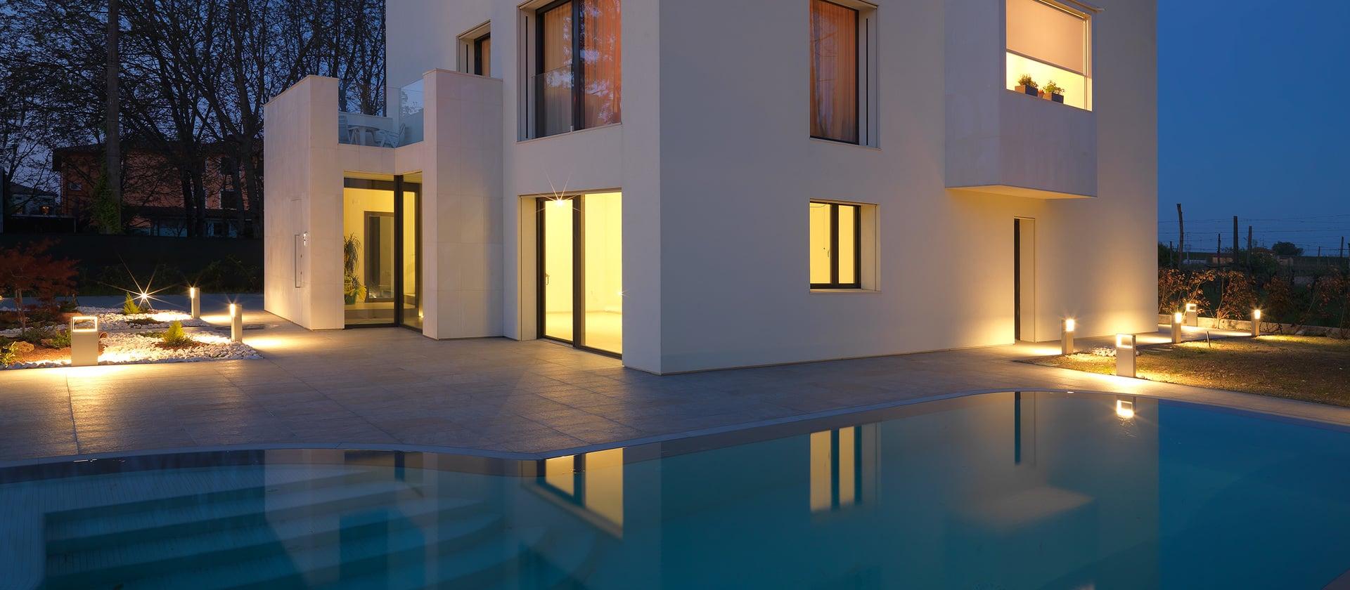 Beleuchtetes Wohngebäude mit Aluminium-Fenster in Abenddämmerung